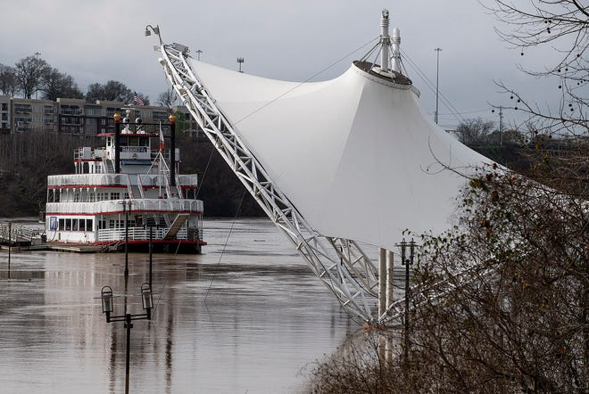 The Alabama River floods Riverfront Park. The Harriot II riverboat floats in the background.