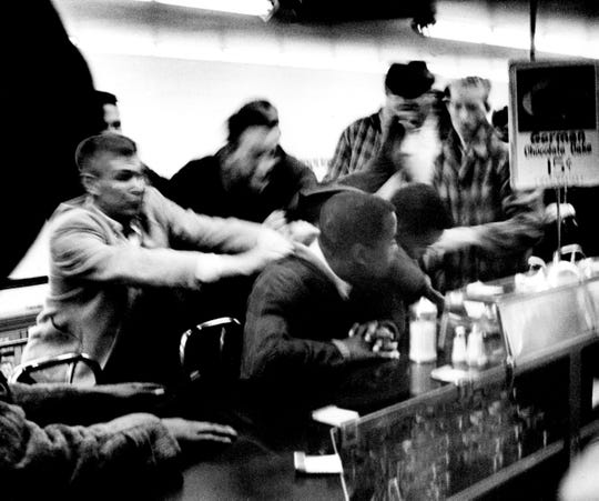 Several men, left, attempt to drag some of the students from the lunch counter where they staged a sit-down against segregation in the downtown Woolworth's store Feb. 27, 1960. Police marched into three variety stores and arrested 73 students seeking lunch counter integration.