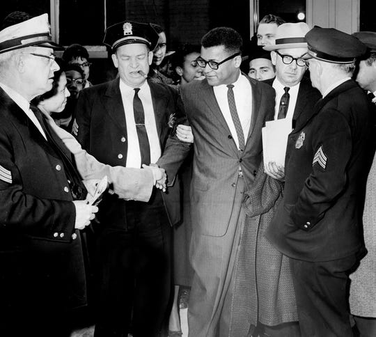 With an arrest warrant in hand, Nashville police arrested the Rev. James Lawson, center, a divinity student who was expelled from Vanderbilt University, in front of the First Baptist Church on March 4, 1960. Lawson, shaking hands with a supporter, was arrested on charges of conspiring to violate the state's trade and commerce law.