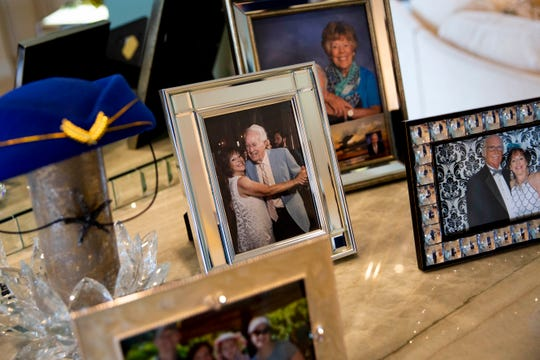 Photos of Jan Madigan with her late father, Lee Raymond Hauser, left, and her husband, Bob Madigan, right, sit on the counter at her home in Naples on Thursday, January 30, 2020. Madigan was a caregiver for her father, who had dementia, until his death in 2017. She says the skills she learned during that time have helped her in taking care of her husband, who is recovering from a severe stroke he suffered during a carotid artery surgery, which left him with aphasia and partially paralyzed.