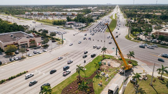 A crane hoists pieces of Marton Varo's sculpture, La Donna, into place at the intersection of Collier Boulevard and U.S. 41 East. The view is looking south toward Marco Island.