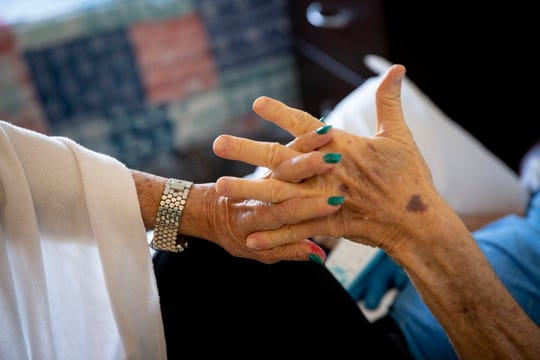 Jan Madigan holds hands with her husband, Bob Madigan, as she says goodbye after a visit at The Glenview at Pelican Bay in Naples on Wednesday, February 5, 2020.