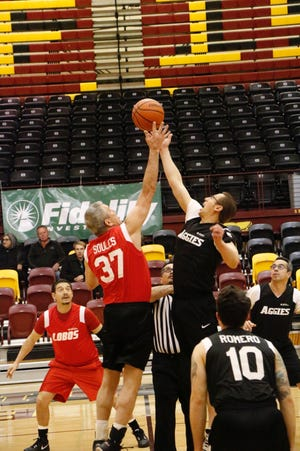 Sen. William Soules (Senate Lobos), left, and Rep. Nathan Small (House Aggies) take the jump ball Tuesday, Feb. 11, 2020, for annual Hoops 4 Hope Senate vs House basketball game.