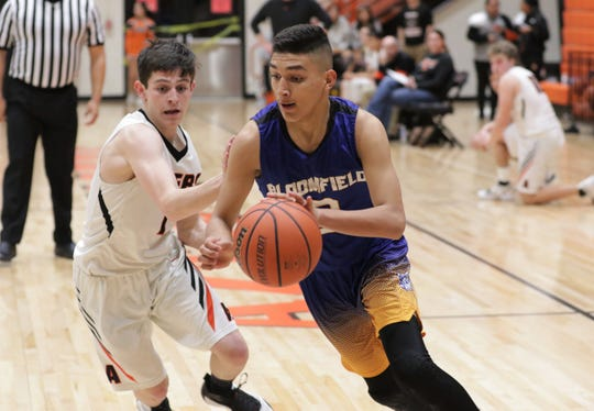 Bloomfield's Raymundo Alcantar drives toward the basket against Aztec's Riley Robert during Tuesday's District 1-4A boys basketball game at Lillywhite Gym in Aztec.