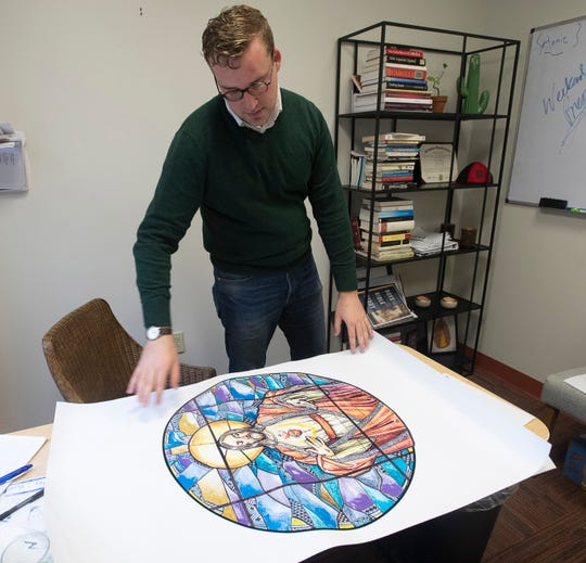 James Reding, coordinator of mission and evangelization at the Cathedral of the Sacred Heart, reviews plans on Wednesday for the cathedral's renovation.
