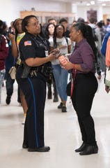 """Pensacola Police Department Officer Mary """"Sharesea"""" Williams-Green receives a lost cellphone from English teacher Tamera Grimsley while patrolling the halls of Pensacola High School on Feb. 12."""
