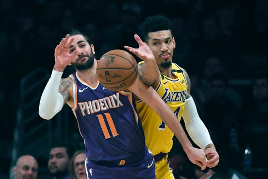 Phoenix Suns guard Ricky Rubio, left, blocks a pass intended for Los Angeles Lakers guard Danny Green during the first half of an NBA basketball game Monday, Feb. 10, 2020, in Los Angeles. (AP Photo/Mark J. Terrill)