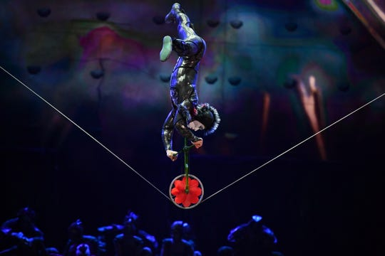 A Cirque du Soleil slackwire performer unicycles across a suspended wire in OVO.