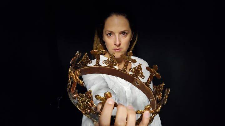 """Co-artistic Director of the Southwest Shakespeare Company, Betsy Mugavero, grasps the crown of the title character she plays in """"Richard II."""""""