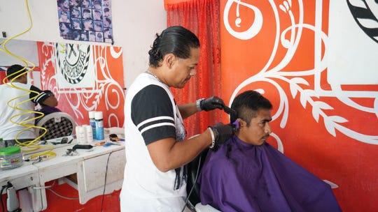 Fotografía fechada el 12 de diciembre de 2019 que muestra al hondureño, Douglas Javier López Flores, realizando un corte de cabello en la comunidad de Ixtepec, en el estado de Oaxaca (México).