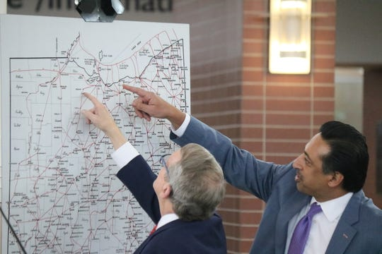 Governor Mike DeWine and Ferzan M. Ahmed, executive director of the Ohio Turnpike, check out a map of Underground Railroad trails throughout Ohio.