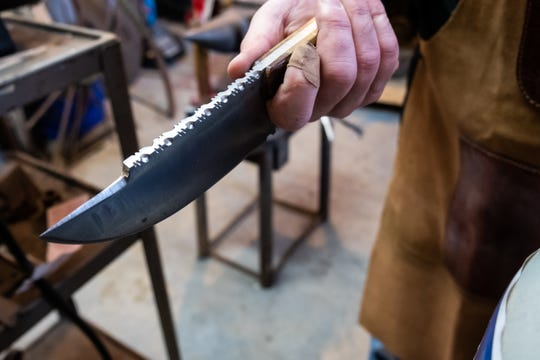 Rob Luther, owner of Bluewater Blacksmith, shows a knife he made with his signature shark's tooth edge.