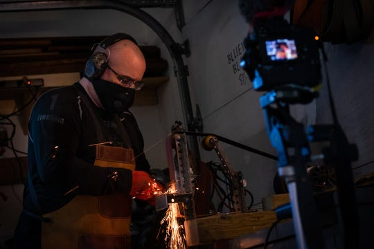 Rob Luther, owner of Bluewater Blacksmith, uses his homemade grinder to grind an edge onto a knife blade Wednesday, Feb. 12, 2020, in his shop in St. Clair. Luther made his grinder with a friend out of parts from a treadmill, skateboard wheels and assorted hardware.
