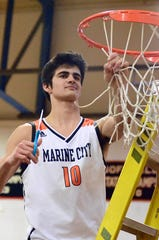 Marine City's Jack Kammer cuts down the net after beating Center Line in a Macomb Area Conference-Bronze boys basketball game on Tuesday, Feb. 11, 2020.