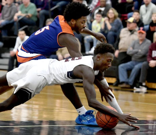 York High's Isiah Carroll, top, and New Oxford's Abdul Janneh dive for a loose ball during semifinal action at Red Lion Tuesday, Feb. 11, 2020. New Oxford won the game 60-54. Bill Kalina photo