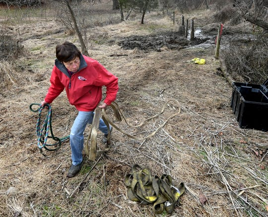 An Equine Rescue Ambulance volunteer gathers tethers from the site where Tonka, a 22-year-old Percheron draft horse, was found trapped in mud, background, in Fawn Township Wednesday, Feb. 12, 2020. After several vain attempts to get the horse to its feet, it was euthanized. Bill Kalina photo