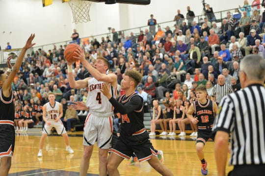 Central York's Gabe Guidinger (4) goes up for a lay up against two York Suburban defenders in a YAIAA semifinal game on Tuesday, February 11, 2020. Central York defeated York Suburban 55-50.