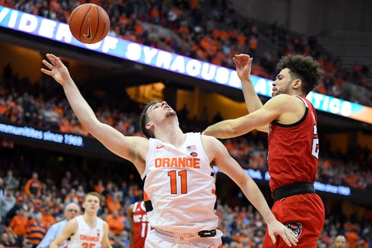 Feb 11, 2020; Syracuse, New York, USA; North Carolina State Wolfpack guard Devon Daniels (right) blocks a shot by Syracuse Orange guard Joe Girard III (11) during the second half at the Carrier Dome.