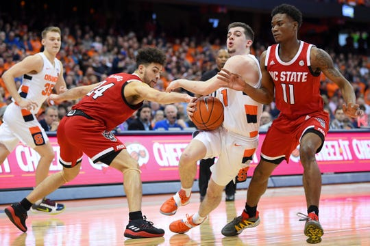 Syracuse Orange guard Joe Girard III (11) drives to the basket between North Carolina State defenders Devon Daniels (24) and Markell Johnson (11) during the second half at the Carrier Dome.