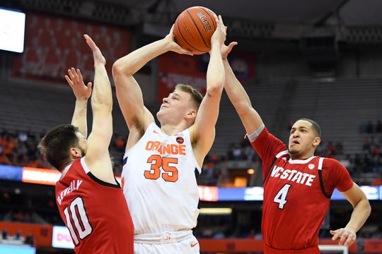 Syracuse guard Buddy Boeheim (35) shoots the ball between North Carolina State Wolfpack guard Braxton Beverly (10) and forward Jericole Hellems (4) during the second half at the Carrier Dome.