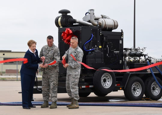 Dr. Carol Bonds, U.S. Air Force Tech. Sgt. Jayton Washington, 312th Training Squadron instructor, and Lt. Gen. Steve Kwast, commander of Air Education and Training Command, cut the ribbon for a new mobile fire pump at the Louis F. Garland Department of Defense Fire Academy on Goodfellow Air Force Base, Texas, March 20, 2019. Thanks to help from Bonds family and the city of San Angelo, Goodfellow was able to purchase four new pumps.