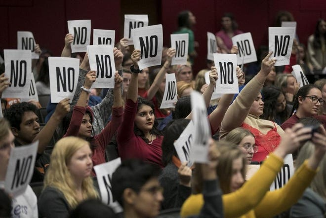 University of Texas students show their disagreement with answers of questions at a town hall meeting about sexual misconduct process and updates at the Belo Center for New Media in January.
