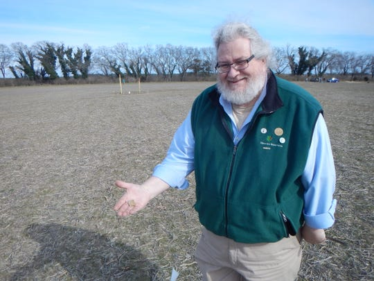 John P. McCarthy, cultural preservation specialist for the Division of Parks and Recreation, holds one of the artifacts found at the Wolfe Neck site — the beginnings of a projectile point.