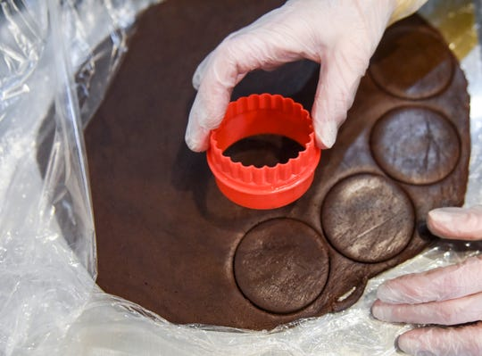 Val Johnson cuts chocolate brownie cookies on Wednesday, Feb. 12, 2020 at Twisted Sisters Sweetz in downtown Sioux Falls, S.D. The family-run bakery hopes to open in March.