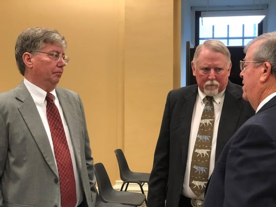 Dale Nolte, left, who oversees efforts to manage feral hogs at the U.S. Department of Agriculture, and Mike Bodenchuk, who oversees similar efforts in Texas, center, speak with a lawmaker after a hearing on feral hog management on Tuesday, Feb. 12, 2020.