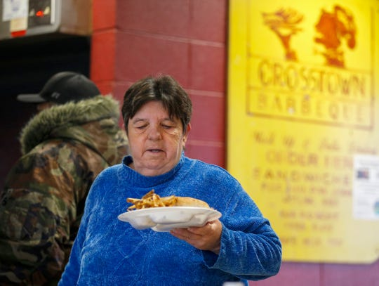 Kay Riggs, a waitress at Crosstown Barbecue, brings food out to a customer on Tuesday, Feb. 4, 2020.