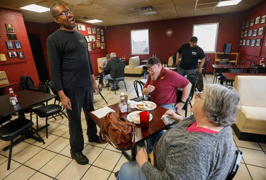 Steve Williams, left, owner of Crosstown Barbecue, laughs as he talks with first-time customers Levi and Mary Miller on Tuesday, Feb. 4, 2020.