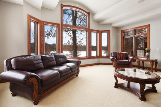 The living room offers picture windows and a multi-leveled ceiling to create interest and drama in the space.