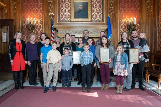Bob and Diane Biadasz accept a 2019-20 Hometown Hero Award Tuesday, Feb. 11, 2020, with members of their family and state Rep. Katrina Shankland at the state Capitol.