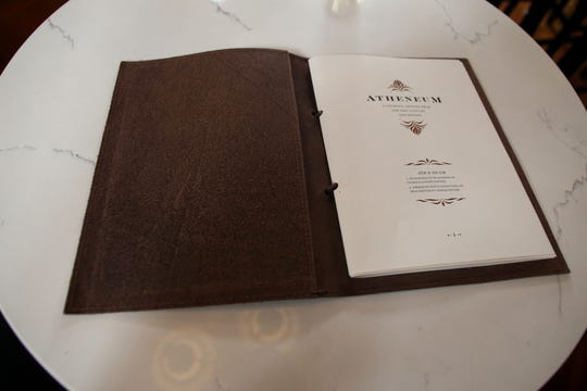The menu for Bar 1903 is bound to resemble a leather-bound book from a library.
