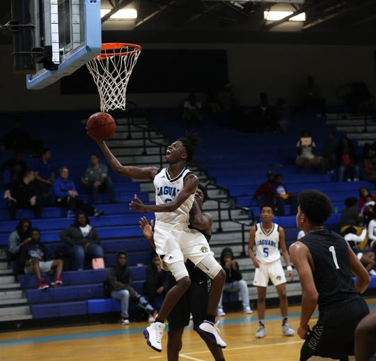 Gadsden County senior guard Ron Stokes hangs in the air for a basket as the Jaguars' boys basketball team beat Suwannee 61-52 during a District 2-4A semifinal on Feb. 11, 2020.