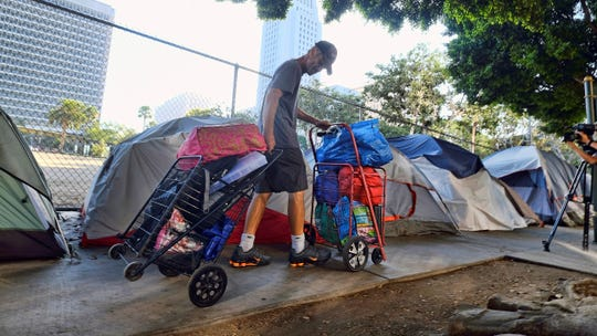 """In this July 1 file photo, a homeless man moves his belongings from a street near Los Angeles City Hall, background, as crews prepared to clean the area. A report issued by the state's Legislative Analyst Office said Gov. Gavin Newsom's recently released 2020-2021 state budget """"falls short of articulating a clear strategy for curbing homelessness in California."""""""