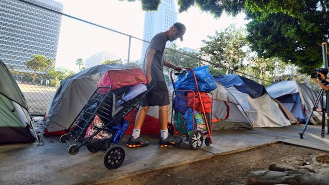 "In this July 1 file photo, a homeless man moves his belongings from a street near Los Angeles City Hall, background, as crews prepared to clean the area. A report issued by the state's Legislative Analyst Office said Gov. Gavin Newsom's recently released 2020-2021 state budget ""falls short of articulating a clear strategy for curbing homelessness in California."""