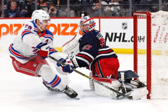 Feb 11, 2020; Winnipeg, Manitoba, CAN;  New York Rangers left wing Chris Kreider (20) scores on Winnipeg Jets goaltender Connor Hellebuyck (37) in the first period at Bell MTS Place.