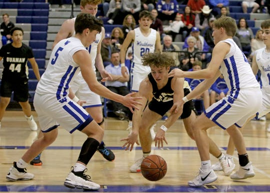 Quanah's Jesse Scofield loses the ball between Windthorst's Gavin Steindberger (5) and Cooper Wolf Tuesday, Feb. 11, 2020, in Windthorst.