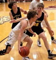 John Glenn's Evan Williams (33) dribbles around Ty Smith (1) and Luke Lyall (10) in Tri-Valley's 59-41 win on Tuesday.