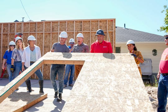 """Host Jesse Tyler Ferguson, designer Carrie Locklyn, and special guest designer Tamara Day (of HGTV's """"Bargain Mansions"""") look on as designers Darren Keefe and Breegan Jane help David Wadman of Wadman Corp. raise a framed wall as construction begins in Ogden, Utah on  a new home for the Barobi family on HGTV's revival of """"Extreme Makeover: Home Edition."""""""