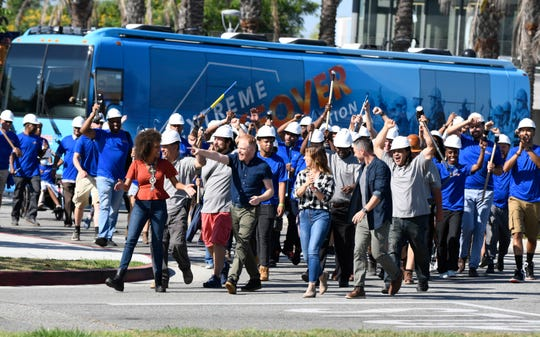 """Host Jesse Tyler Ferguson leads the charge with designers Breegan Jane, Carrie Locklyn and Darren Keefe as volunteers march to surprise the Washington family in West Athens, California, in an episode of HGTV's """"Extreme Makeover: Home Edition."""""""