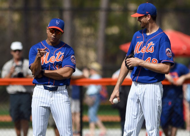 Mets manager Luis Rojas talks with pitcher Jacob deGrom during a workout Wednesday.