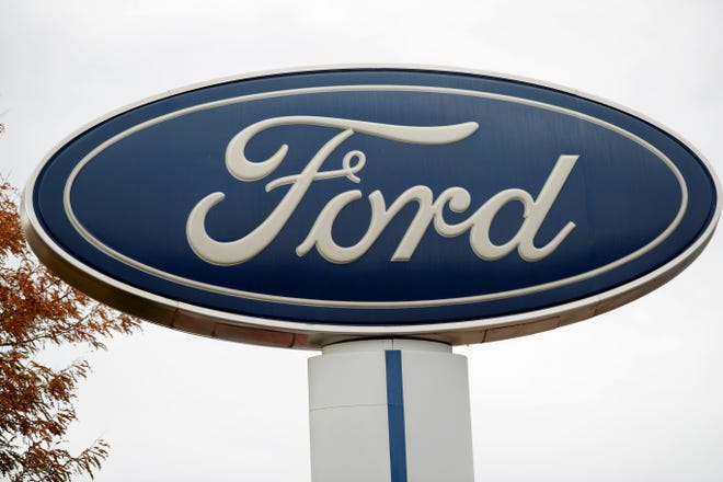 In this Oct. 20, 2019, file photo, the company logo stands over a long row of unsold vehicles at a Ford dealership in Littleton, Colo.