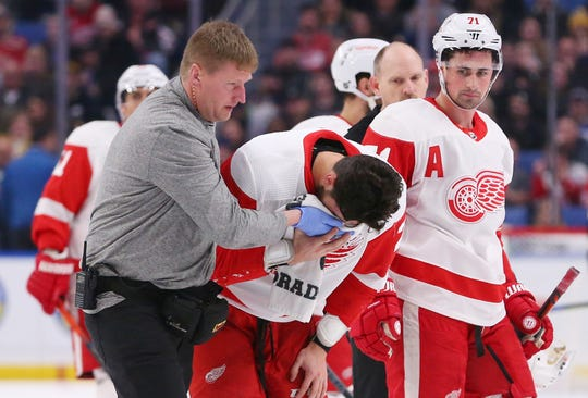 Detroit Red Wings forward Brendan Perlini is helped off the ice.