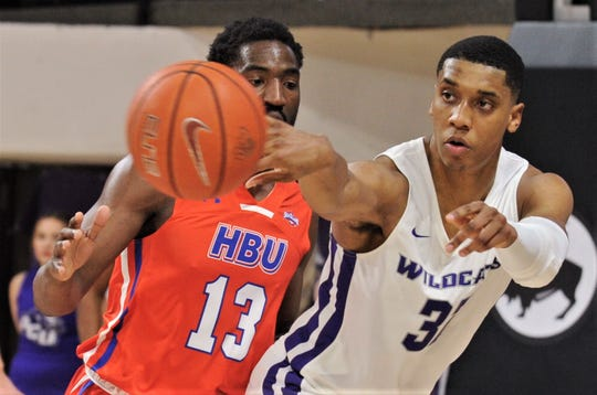 ACU's Joe Pleasant, right, passes the ball in front of Houston Baptist's Phillip McKenzie in the second half Wednesday.