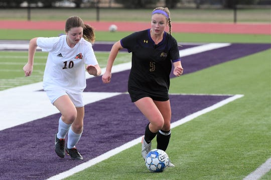 Wylie's Marianna Deynzer (5) gets past Aledo's Arwen Wise (10) with the ball during the District 4-5A opener at Bulldog Stadium on Wednesday. The Lady Bulldogs fell 3-1.