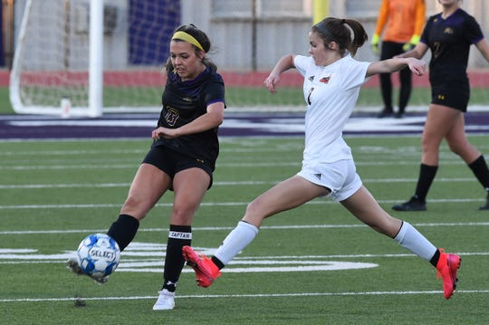 Wylie's Kalli Hanson (13) delivers a pass past an Aledo defender during a game in February. Hanson is the lone senior for the Lady Bulldogs this season. If the season restarts, Wylie is in a playoff position for the first time as a Class 5A program.