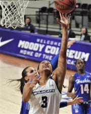 ACU's Dominique Golightly (3) drives for a basket against Houston Baptist in the first quarter.