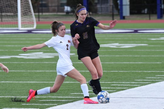 Wylie's Ella Beard (18) tries to avoid a tackle from Aledo's Madison Bilbia (2) during the District 4-5A opener at Bulldog Stadium on Wednesday. The Lady Bulldogs fell 3-1.